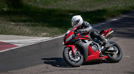 Man riding motorcycle in asphalt road curve with rural,motorcycle practice leaning into a fast corner on track 写真素材