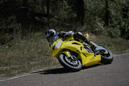 Man riding motorcycle in asphalt road curve with rural,motorcycle practice leaning into a fast corner on track 写真素材 - 150726989