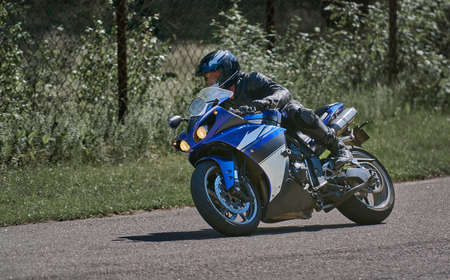 Man riding motorcycle in asphalt road curve with rural,motorcycle practice leaning into a fast corner on track 写真素材 - 150727091