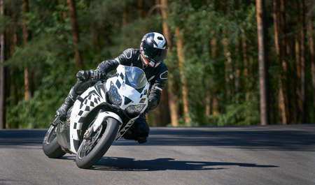 Man riding motorcycle in asphalt road curve with rural,motorcycle practice leaning into a fast corner on track 写真素材 - 150727585