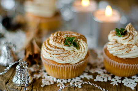 Christmas cupcakes with cream on a table decorated with Christmas decorations photo