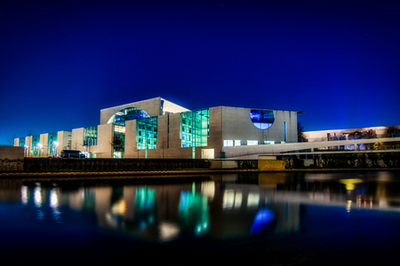 Chancellery in Berlin at night with light reflections on the water of the Spree