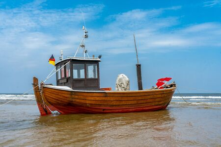 old wooden fishing boat at low tide on a beach Stock Photo