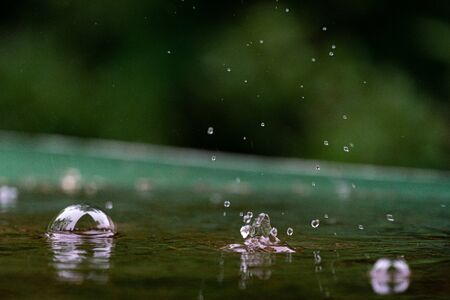 raindrops and water bubbles in a puddle on a green table with bokeh background