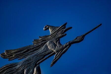 Veleta de una bruja volando en una escoba con un cielo azul oscuro como fondo