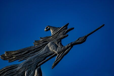 Weather vane of a witch flying on a broom with a dark blue sky as background