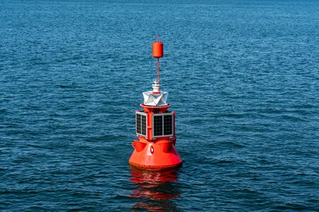 electric red buoy with solar panel anchored in the baltic sea