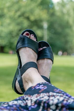 Putting up female feet with sandals with a park background for a break