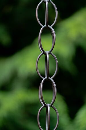 Close up of metal chain links and a blurry green bokeh background