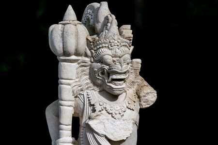 slightly damaged garden statue of a balinese temple guardian missing an arm 写真素材