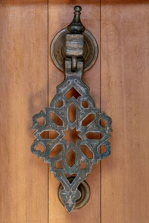 Elaborate ancient brass doorknocker with filigree details