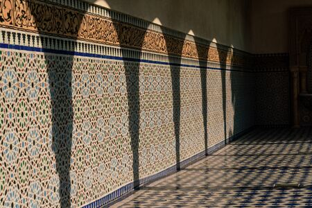 Shadows of pillars on a mosaic tiled wall in full sunshine Stock Photo