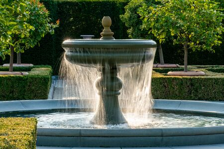 Sprinkling water of a fountain with detailed water drops glinstering in bright sunshine