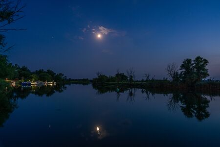 Nighshot of the harbour in Strodehne with moon reflecting on water of the river Havel in Havelaue, Brandenburg, Germany