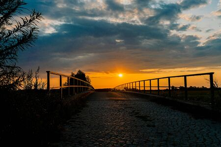 A bridge at sunset leading into the light in Guelpe, Brandenburg, Germany