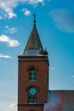 Church in Guelpe, Germany with two storks breeding on the clock tower roof Stockfoto
