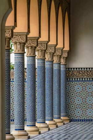Oriental looking columns with blue mosaic pattern and a tiled floor with oriental patterns