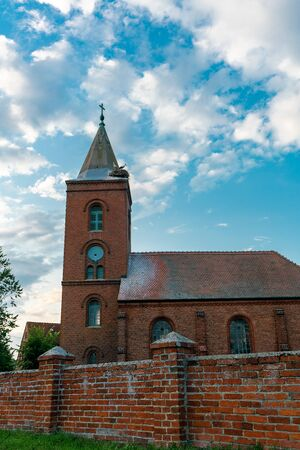 Church in Guelpe, Germany with two storks breeding on the clock tower roof Stockfoto - 130064652