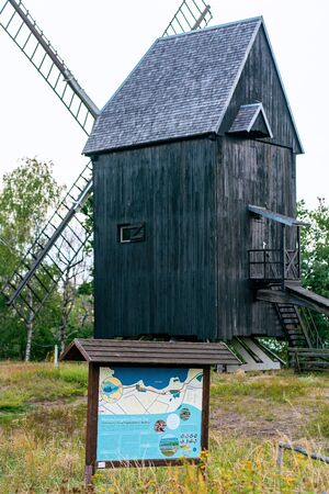 Old wooden windmill in Prietzen Germany with board showing the nature reserve at Guelper See