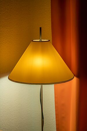 Lamp with a yellow shade and an orange curtain in the background glowing with cosy golden light