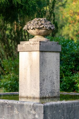 Stone monument with a basket full of flowers as part of a water fountain in bright sunshine