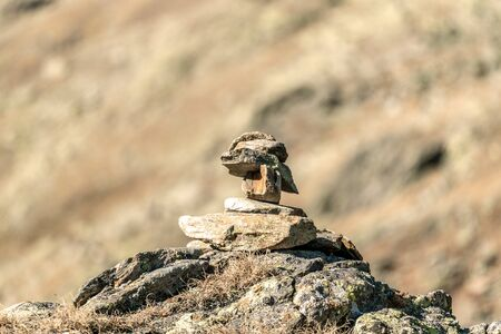 Beautiful close up of a small cairn high up on a mountain summit at Timmelsjoch  with a blurry bokeh background Stock fotó