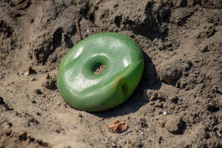 Abandoned toys - a childs green disk toy found as trash along a path in nature