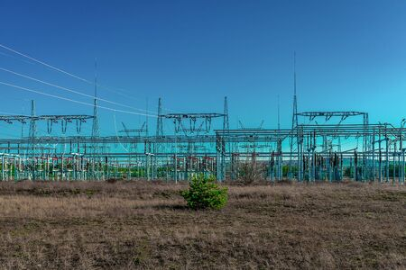 Modern electric power substation in Poland with a bare field and one single green bush in the foreground- contrast nature-engineering