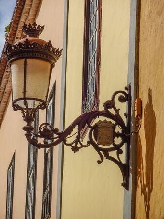 Weathered old iron lamp on the walls of a meditereanean house in Spain with decorative elements Stock Photo