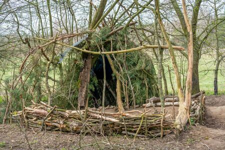 Small round hut at Tegeler Fliess build witch wood and branches Standard-Bild