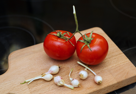 two tomatoes and young garlic on wooden cutting board