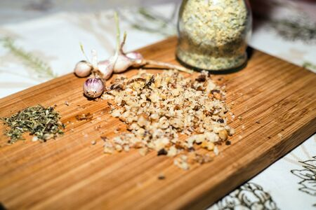 Spices and chopped walnuts on wooden board Stock Photo
