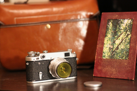 ferrous: old iron camera on the background of leather cases and picture frames