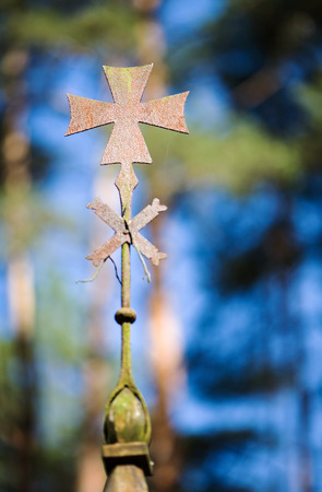 the Maltese cross on the spire of the old Church in the woods Editorial