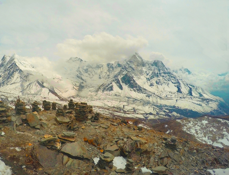 severe: On top of mountain in Himalaya, Nepal. Huge ice peaks of Everest. Snow landscape with rocks and stone pyramids. Trekking in Sagarmatha. Trekker and mountaineer memorable marks. Sport in severe climate