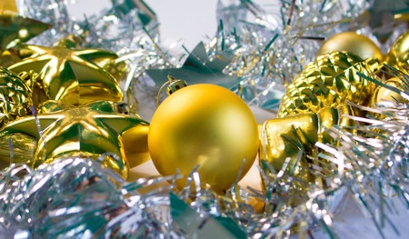 macrophoto: Christmas or New Year photo background with silver ribbon and gold fir tree toys. Festive winter holiday composition. Christmas greeting card. New Year banner template. Silver and gold decor picture