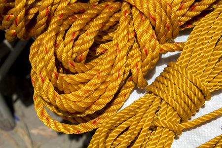 tether: Yellow rope in piles on the market. Braided rope for sailing ship, house works, construction. Rope bunch image. Horizontal image for houseworks, reconstruction, DIY project, hand tool. Gardening cord
