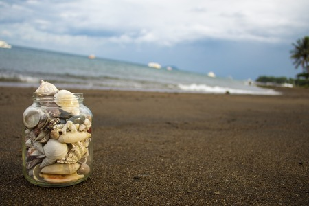 experimental: Seashells collection on the sand beach. Experimental composition with diagonal horizon. Tropical landscape with sea and white boats with place for text. Stock Photo