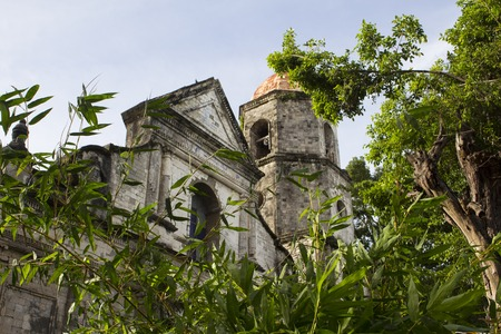 Old church in European style beneath green trees. Spanish dome in gothic style. Remains of colonial regime in Philippines. Architecture style of Spain in former dominions. Historical building in park