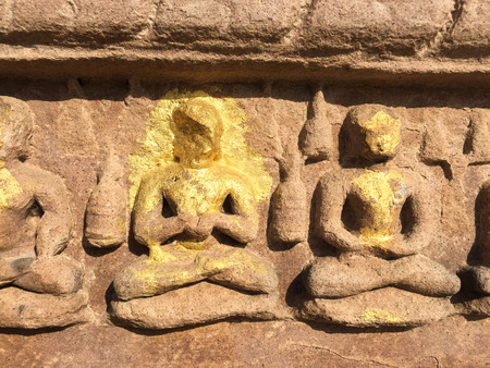 ancient yoga: Stone carved Buddha with gold leaf. Stone carved relief on ancient hindu temple. Traditional indian art. Buddhist decoration. India place of interest. Yoga lotus pose of meditating people