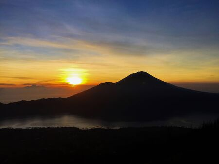 Sunrise in the mountains. Rising sun in orange and silver sky, fluffy clouds, distant mountains and volcanic lake. Morning dawn landscape. Natural background for print, poster or web design