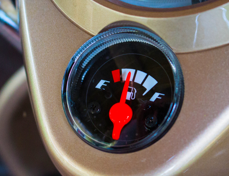 run out: Fuel gauge on motorcycle dashboard. Round fuel gauge with red arrow. Fuel gauge show petrol run out. Empty gas tank. Transport closeup photo. Motorbike electric gear. Concept image for economic crisis