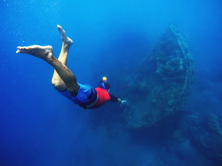 snorkelers: Diving to the shipwrecks, snorkeler in the deep blue sea, life underwater near the coral reef, man snorkeling in mask, freediving sport activity, sportsman underwater, diving in warm sea, Amed, Bali