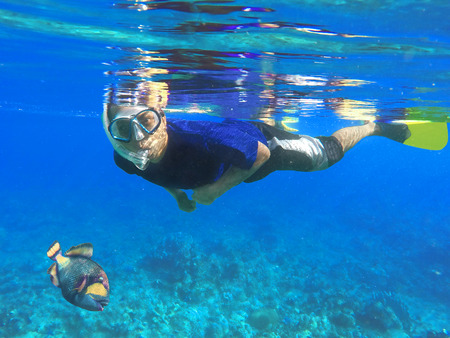 freediving: Asian snorkel and big fish under blue water during snorkeling lesson near coral reef, snorkeling with triggerfish, indonesian snorkel in mask, diving to coral reef, Nusa Penida, Bali, Indonesia