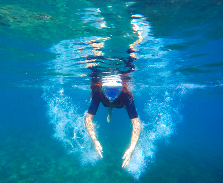 Woman under water makes bubbles, snorkel woman snorkeling in black mask, woman face in mask, tropical sea snorkeling, summer vacation activity, girl swimming, young girl in sea, underwater wings