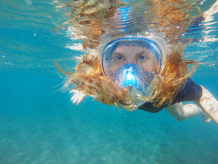Beautiful woman under water before dive to coral reef. Red hair girl snorkeling in blue mask. Female snorkel in tropical sea. Summer vacation sport. Young and sportive person. Philippines sea activity