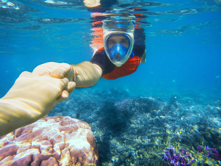 Snorkeling couple holding hands in blue ocean near coral reef, hands together, snorkel couple, snorkeling mask, underwater swimming, summer holiday activity, snorkeling in coral reef, Philippines