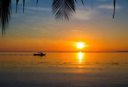 Seaside sunset with palm leaf silhouettes. Tropical sunset landscape with boat in water. Beautiful nature of tropical island. Sea view with sun reflection in water. Orange sunset wanderlust photo Stock Photo