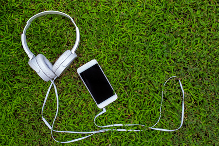 White headphones and white smartphone on green grass. Summer lawn with personal gadget. Listen to music concept photo. White earphones in grass. Black screen cellphone. Banner template with text place