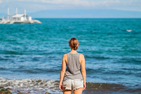 Woman in shirt and shorts on beach. Bright photo of young girl watching cruise boat. Seaside vacation travel vintage banner template. Turquoise water of tropical lagoon. Sunny day by sea background Stock Photo